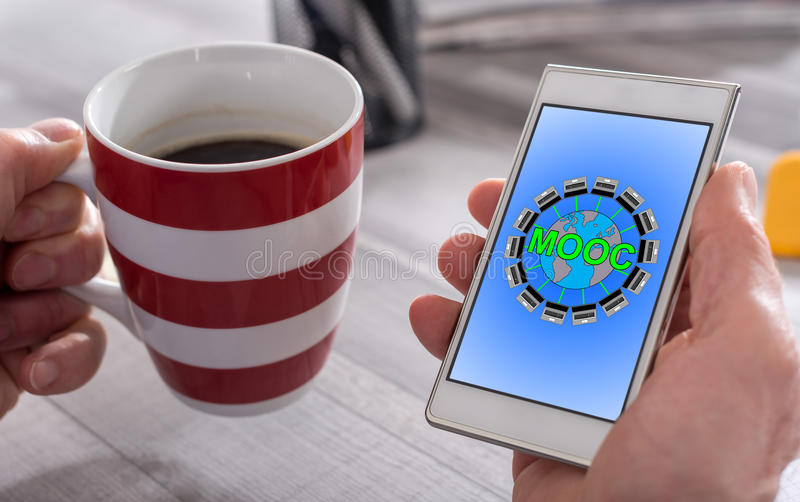 Mooc concept on a smartphone. Male hand holding a smartphone with mooc concept royalty free stock images