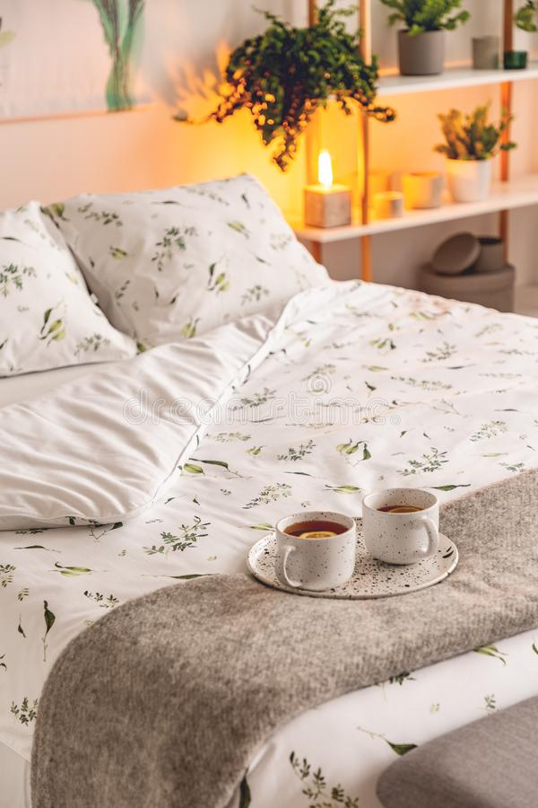 A mood created by a night lamp standing beside a bed dressed in green plants on white pattern linen and pillows in a natural style stock photography