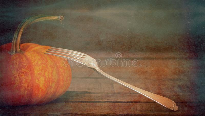 Pumpkin with fork. A moody, candle-lighted pumpkin gourd still life centerpiece on a table with space above for copy, text, or words stock photos
