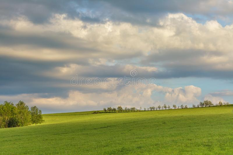 Moody cloudy sky over green hills royalty free stock images