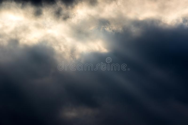 Moody dark sky. Soft background image with crepuscular rays of s. Unlight through cloud. Natural light and dark variegated texture backdrop stock image