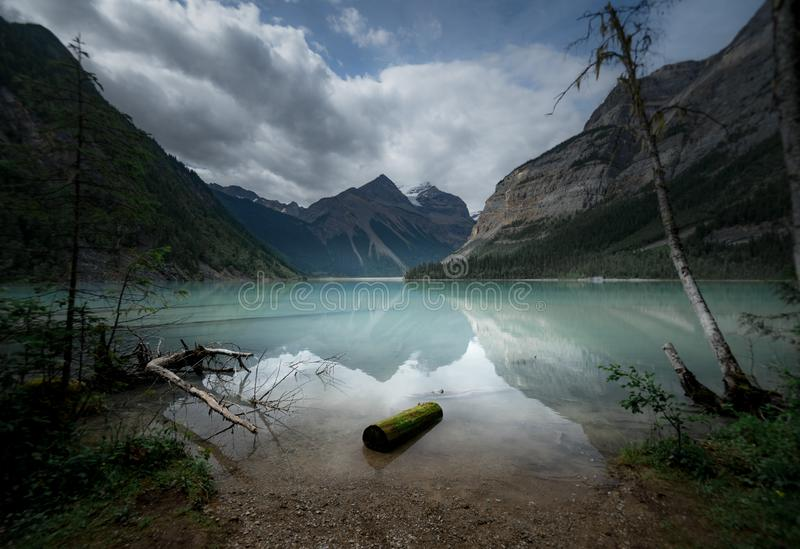 A moody day on the shores of an alpine lake blue with glacial silt in the rocky mountains stock photos