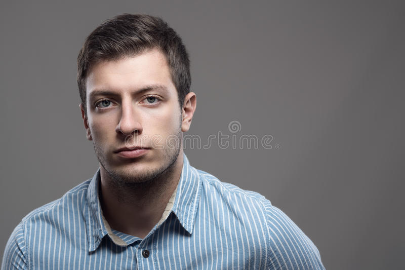 Moody dramatic portrait of serious young man in blue shirt looking at camer. A with copyspace stock photos