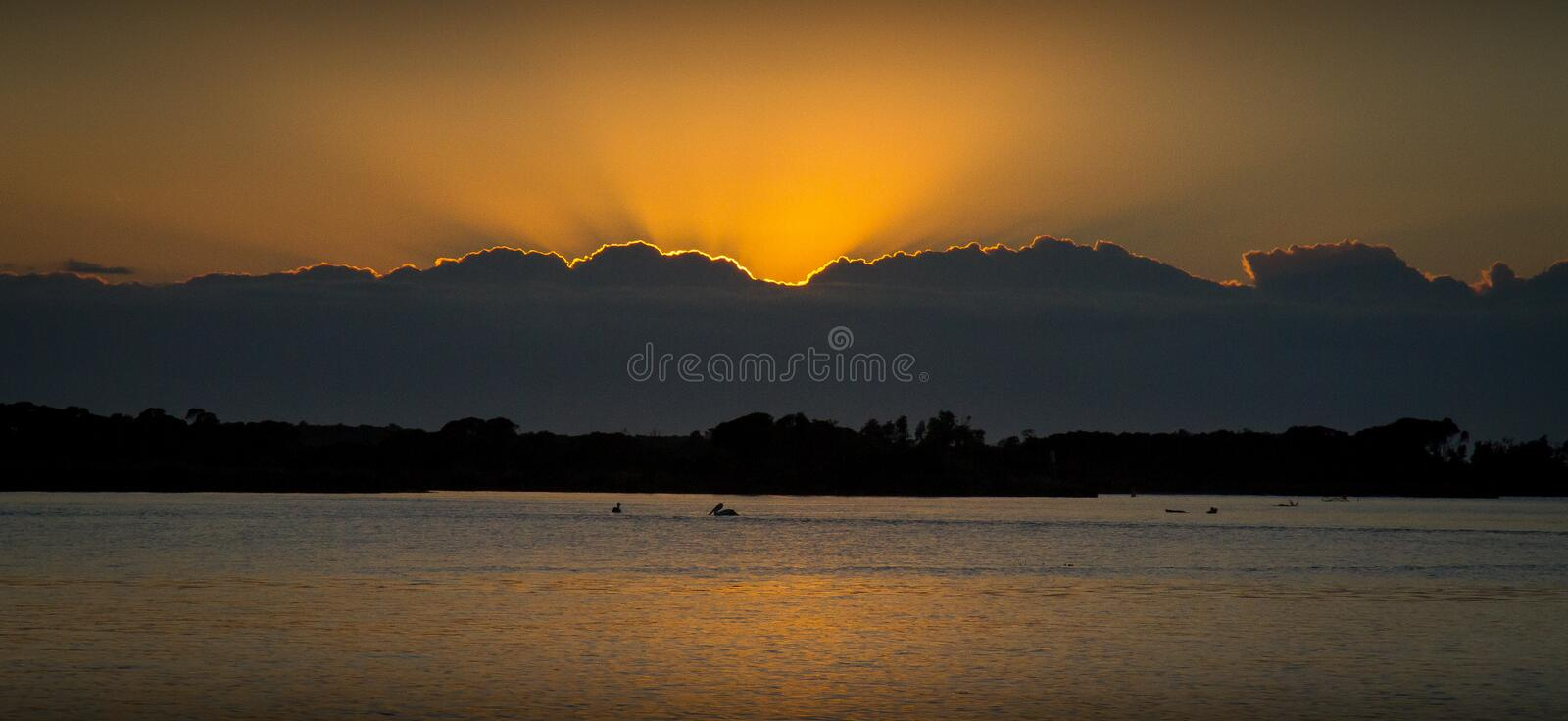 Moody estuary sunrise over the sand and mud flats stock images