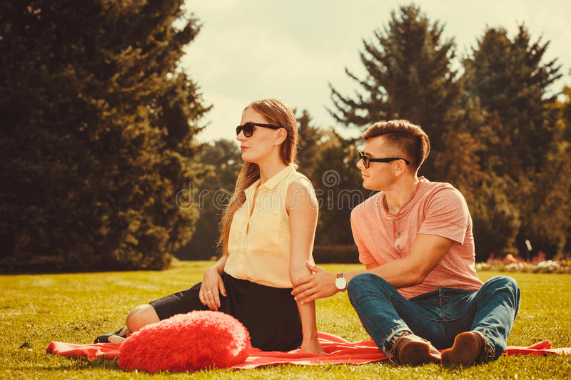 Moody girl with boyfriend in park. royalty free stock images