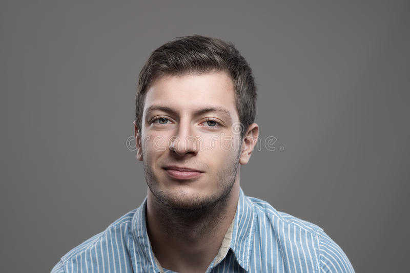 Moody headshot portrait of young man in blue shirt with smirk smile stock photography