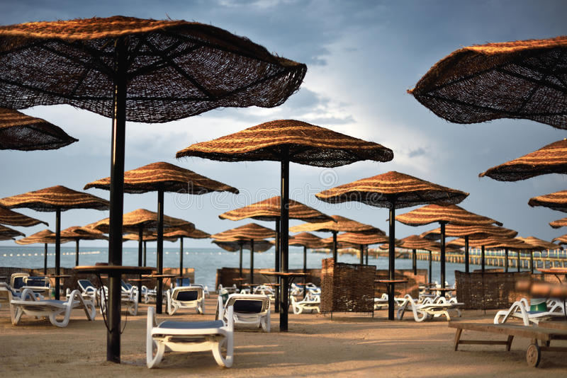 Moody image hotel beach area with umbrellas and sun loungers cloudy weather, horizontal royalty free stock image