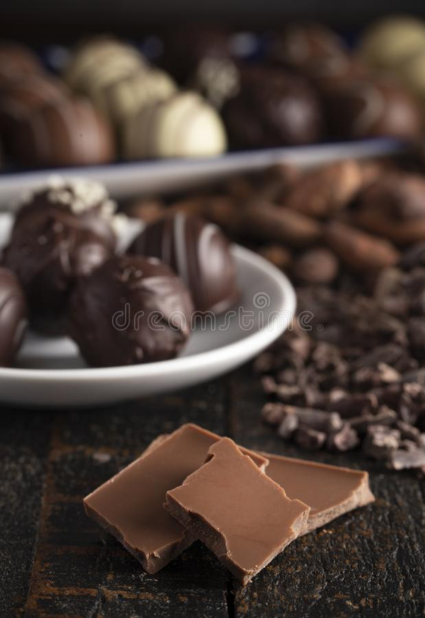 A Moody Image of Various Types of Chocolate on a Wooden Table. A Moody Image of Various Types of Chocolate on a Rustic Wooden Table stock image
