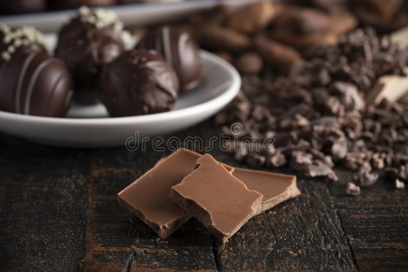 A Moody Image of Various Types of Chocolate on a Wooden Table. A Moody Image of Various Types of Chocolate on a Rustic Wooden Table stock images