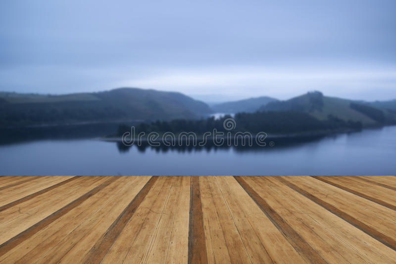 Moody landscape image of lake pre-dawn in Autumn with haunting f. Moody landscape image of lake pre-dawn in Autumn with wooden planks floor stock photography