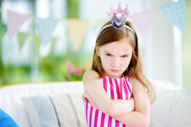 Moody little girl wearing princess tiara feeling angry and unsatisfied royalty free stock images