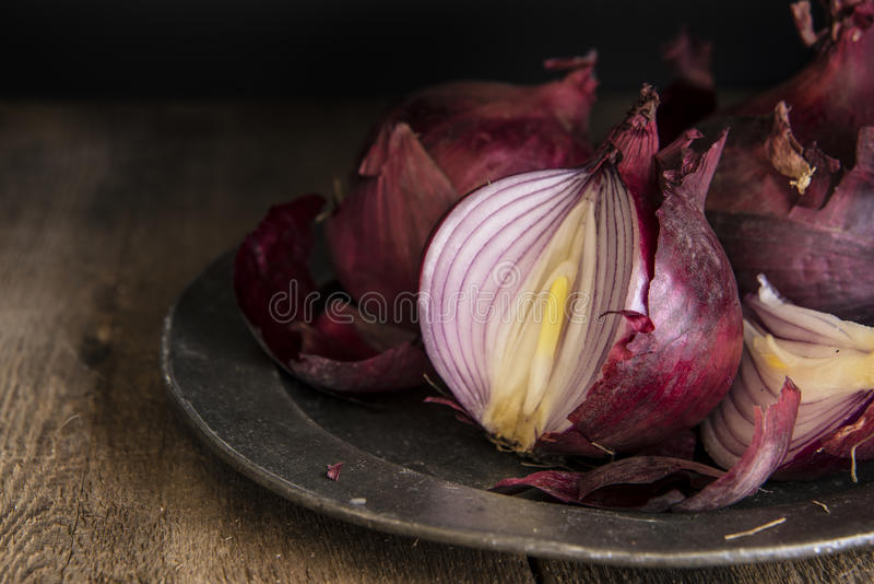 Moody natural light vintage retro style image of fresh red onion. Moody natural light vintage style image of fresh red onions stock photography