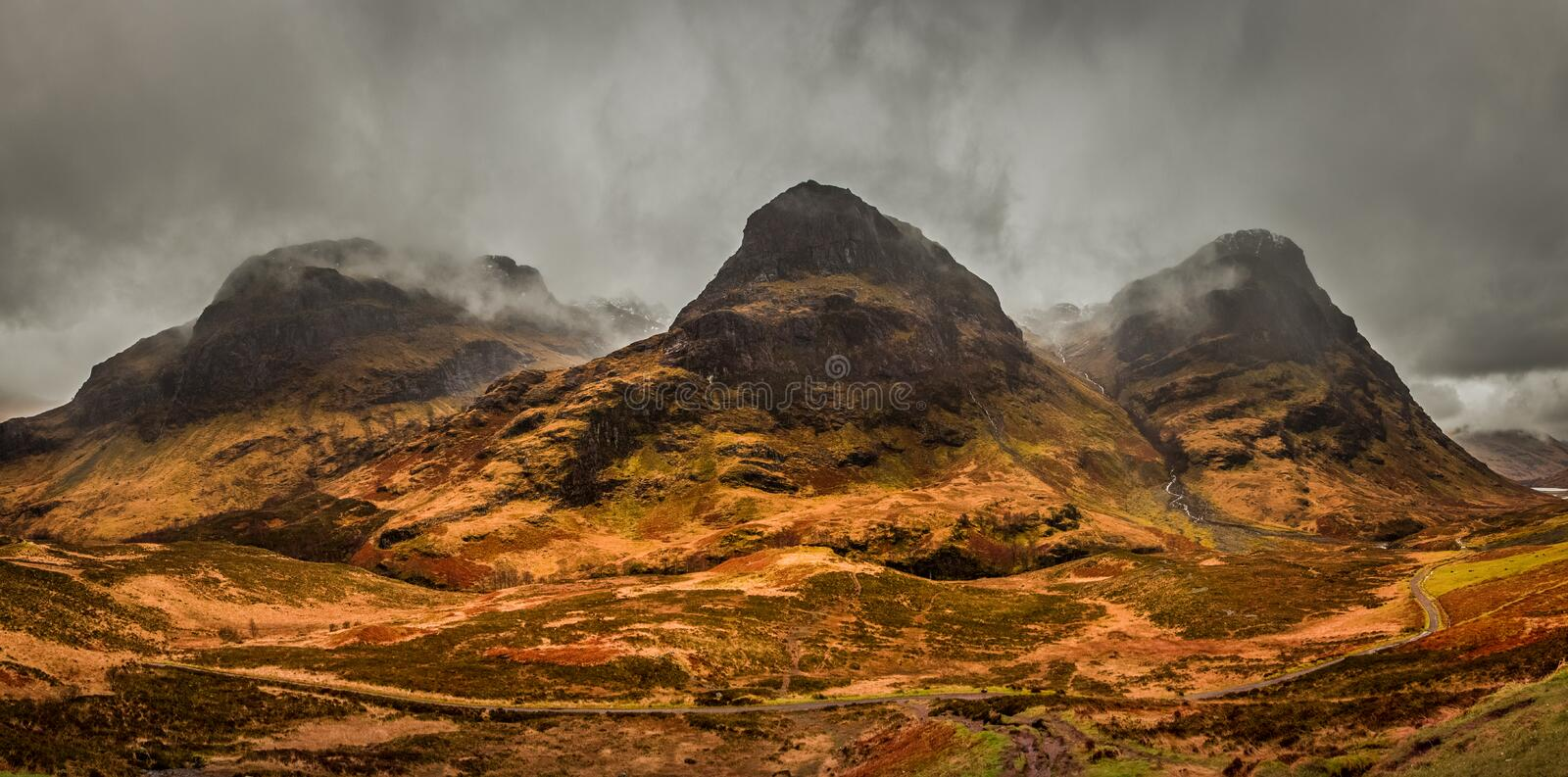 A moody panoramic of the Three Sisters mountains in Glencoe. Scotland. A moody panoramic of the Three Sisters mountains in Glencoe, covered in rusty moorlands royalty free stock photography