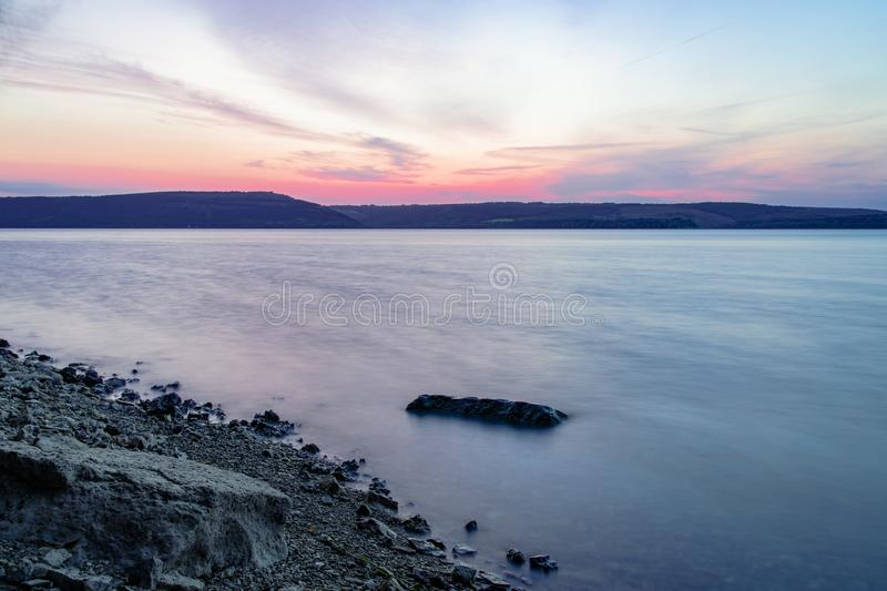 Moody and peaceful long exposure stone coast line landscape with fuzzy smooth lake water surface foreground and horizon main land stock photos