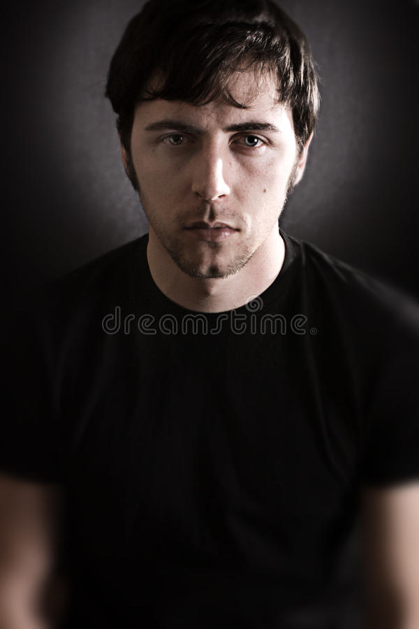 Moody Portrait. A close up of a young man in front of a dark background stock photos