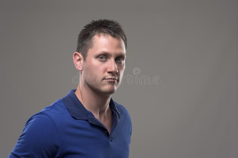 Moody portrait of serious confident young man in blue polo shirt looking at camera. On gray background stock photography