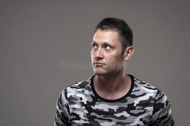 Moody portrait of serious young athletic man in military shirt looking away at copyspace royalty free stock image