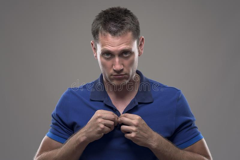 Moody portrait of young annoyed man buttoning polo shirt collar and looking at camera. Over gray background royalty free stock images
