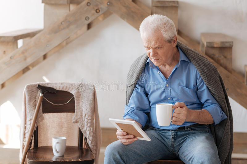 Moody senior man missing his wife. We used to drink tea together. Moody unhappy senior man looking at the photo of his wife and missing her while having tea royalty free stock photography