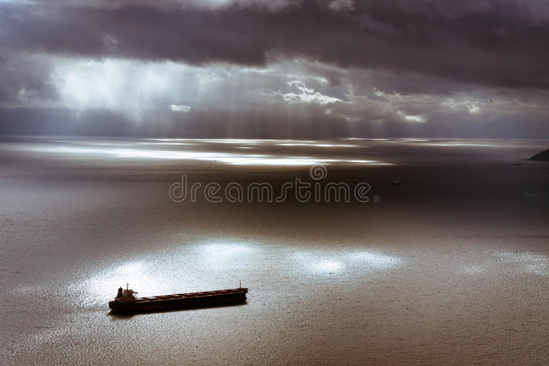 Moody sky and Mediterranean Sea with ship leaving Gibraltar stock images