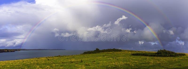 Moody sky met volledige regenboogbrug aan de Britse kust, Zuid-Wales, Verenigd Koninkrijk stock foto's