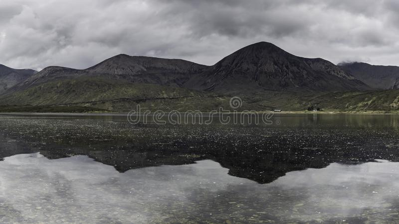 Moody sky over mountain peaks reflecting in lake surface. Reflection of mountain range in lake.Moody sky over peaks.Panoramic landscape image perfect for print royalty free stock photo
