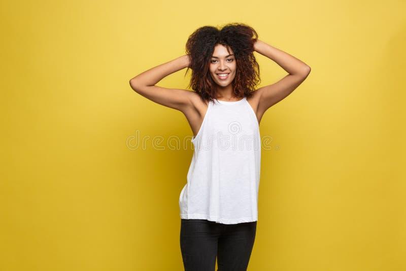 Mooi aantrekkelijk Afrikaans Amerikaans vrouw het posten spel met haar krullend afrohaar Gele studioachtergrond De ruimte van het stock afbeelding