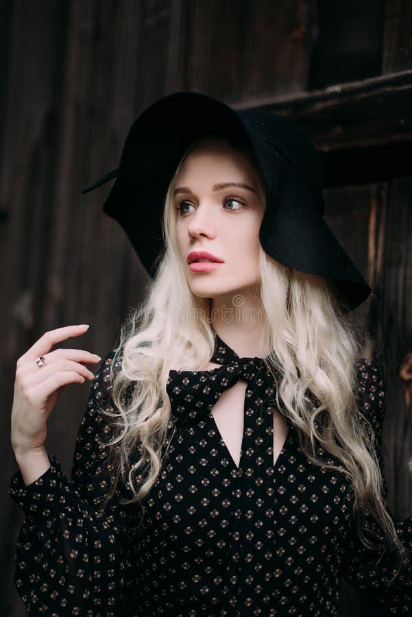 Mooi aantrekkelijk en modieus meisje die het zwarte hoed bevindende stellen in stad dragen Naakte make-up, het best dagelijks kap stock foto's