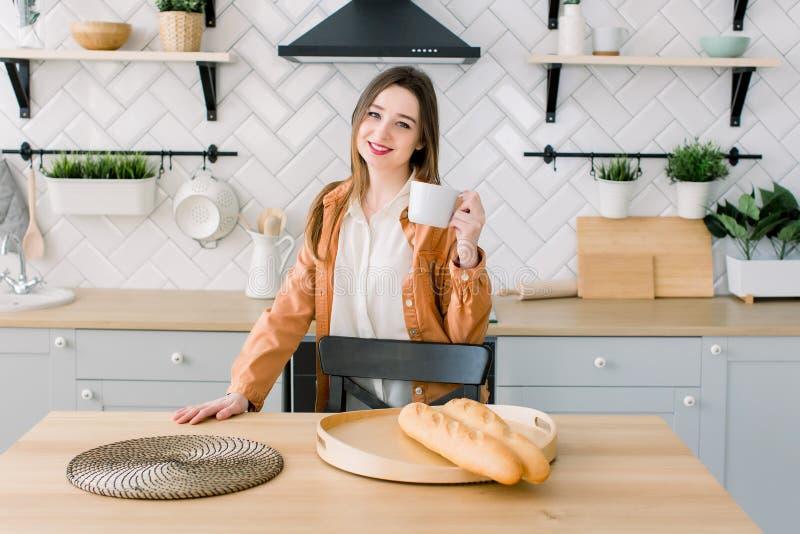 Mooi aantrekkelijk wijfje met de mok van de koffiethee in keukenkleur, huisvrouw, huis, vrouw, moeder stock foto