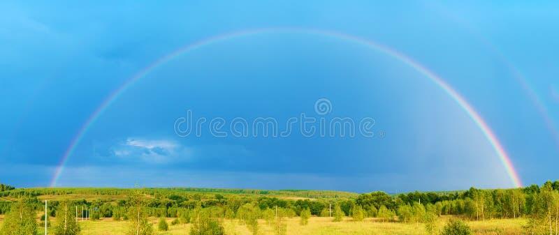 Mooi aardlandschap met dubbele volledige regenboog boven gebiedspanorama stock foto's
