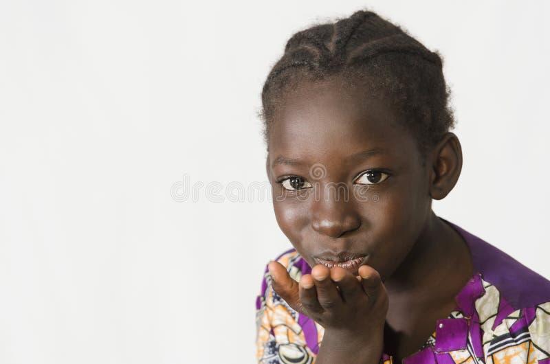 Mooi Afrikaans meisje die die een kus blazen, op wit wordt geïsoleerd royalty-vrije stock fotografie
