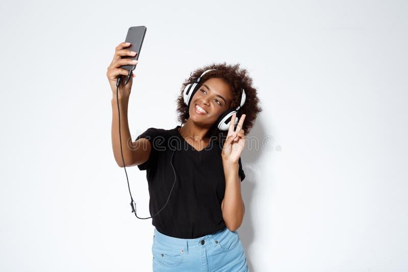 Mooi Afrikaans meisje die in hoofdtelefoons selfie over witte achtergrond maken stock foto