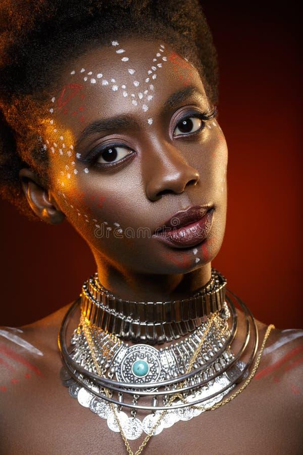 Mooi afromeisje met tekeningen op huid stock fotografie