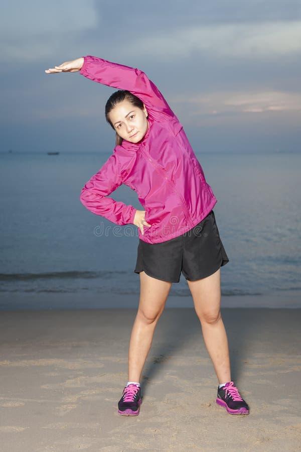 Mooi aisan meisje die oefeningen op het strand doen Tegen de achtergrond van het overzees stock afbeeldingen