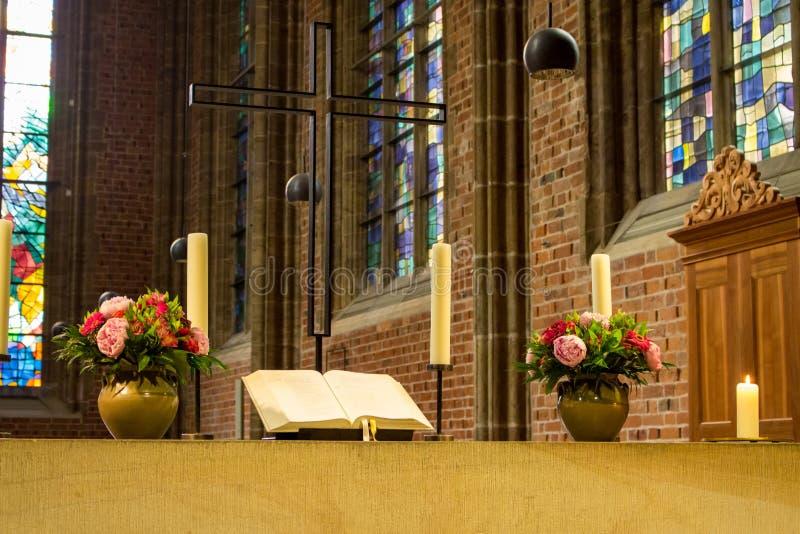 Mooi altaar in katholieke kathedraal Open heilige bijbel met bloemen, kaarsen en kruis Elegante decoratie van kerk stock foto's