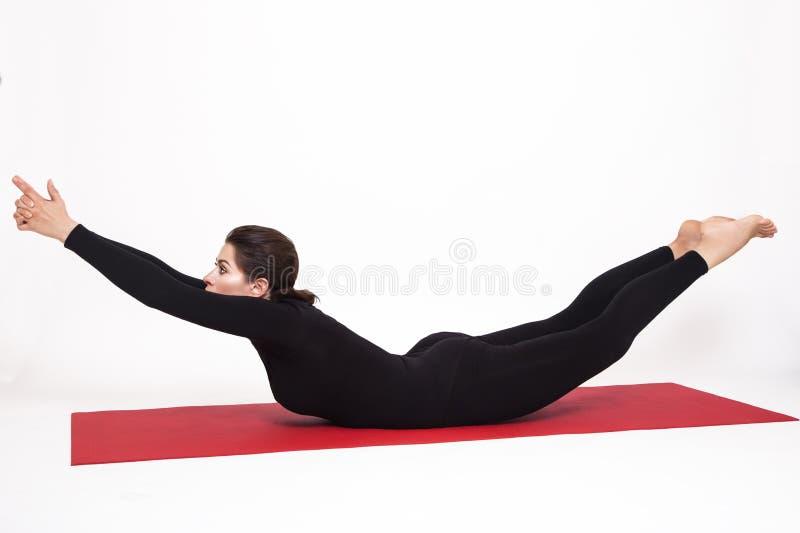 Mooi atletisch meisje in een zwart kostuum die yoga doen de asanaboot van viparitanaukasana stelt Geïsoleerdj op witte achtergron royalty-vrije stock foto