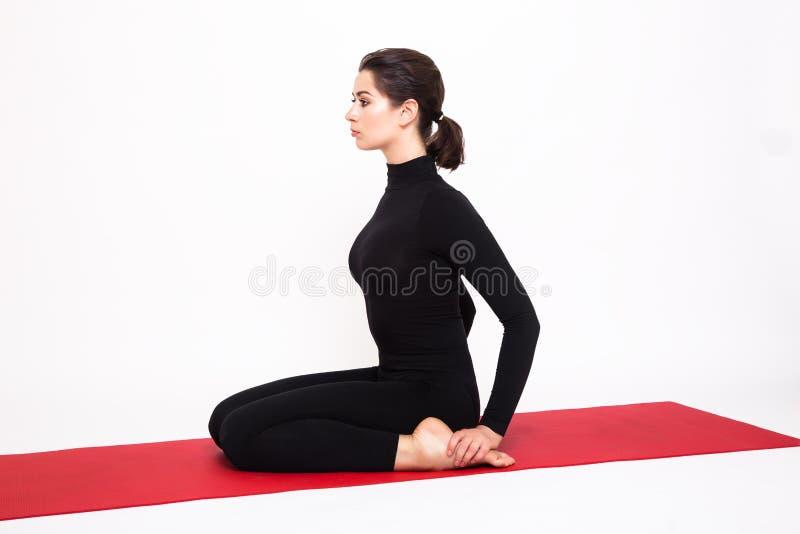 Mooi atletisch meisje in een zwart kostuum die yoga doen De held van Virasanaasana stelt Geïsoleerdj op witte achtergrond stock afbeeldingen