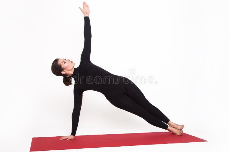 Mooi atletisch meisje in een zwart kostuum die yoga doen de salie van vasishthasanaasana stelt Geïsoleerdj op witte achtergrond stock foto's