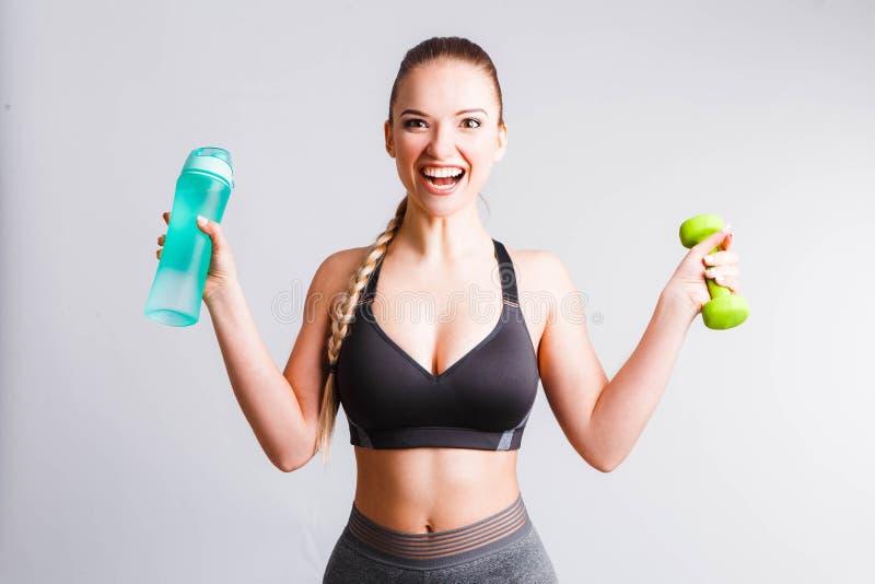 Mooi atletisch meisje met een blauwe schudbeker op een lichtgrijze achtergrond stock afbeelding