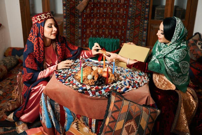 Mooi azeri vrouwen en novruz dienblad met traditionele gebakjeshekerbura en pakhlava royalty-vrije stock foto