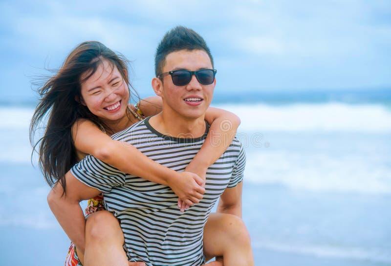 mooi Aziatisch Chinees paar met vriend dragende vrouw op haar rug en schouders bij strand glimlachen gelukkig in liefde stock foto