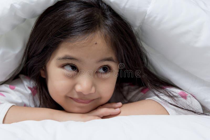 Mooi Aziatisch kind die op het bed bepalen royalty-vrije stock afbeelding