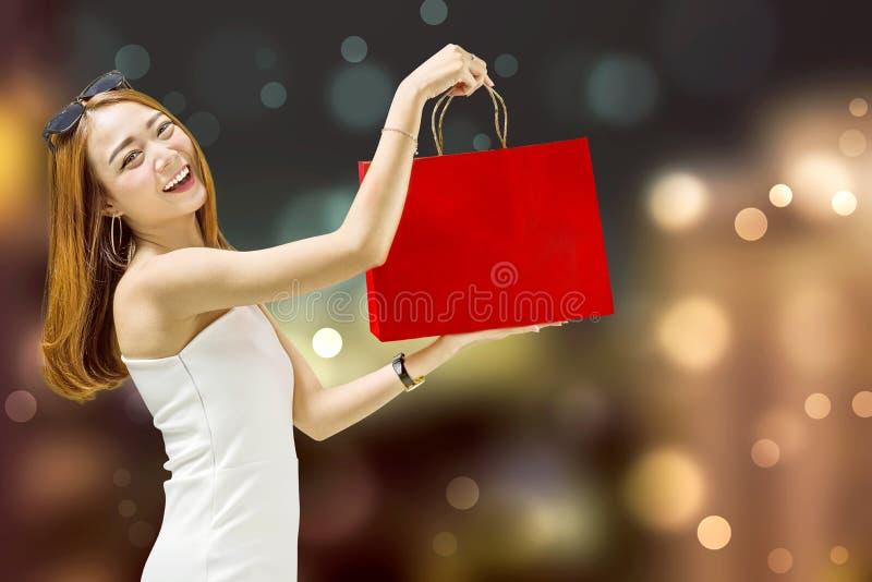 Mooi Aziatisch meisje die haar het winkelen zakken tonen stock fotografie