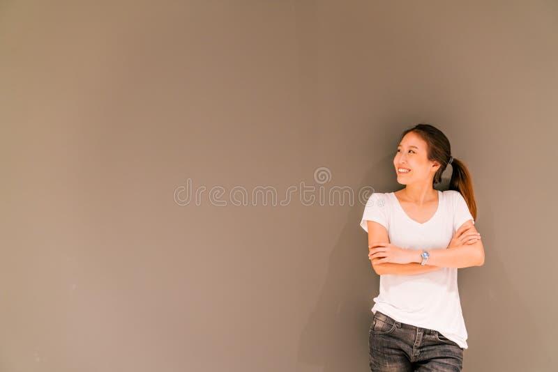 Mooi Aziatisch meisje die zich op grijze muurachtergrond bevinden, die exemplaarruimte bekijken royalty-vrije stock foto