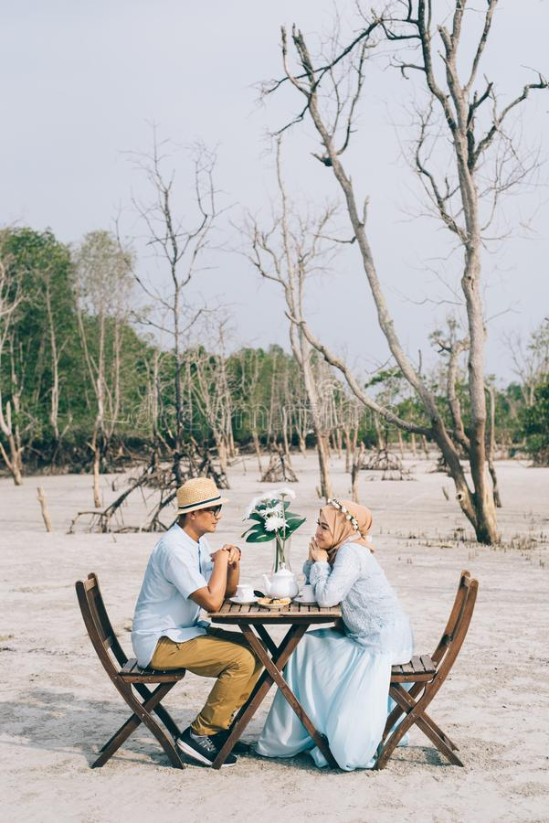 Mooi Aziatisch paar die een romantisch ogenblik van geluk openlucht met picknicklijst en stoel hebben stock afbeeldingen