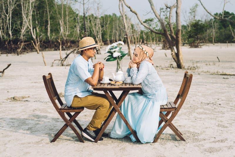 Mooi Aziatisch paar die een romantisch ogenblik van geluk openlucht met picknicklijst en stoel hebben stock afbeelding