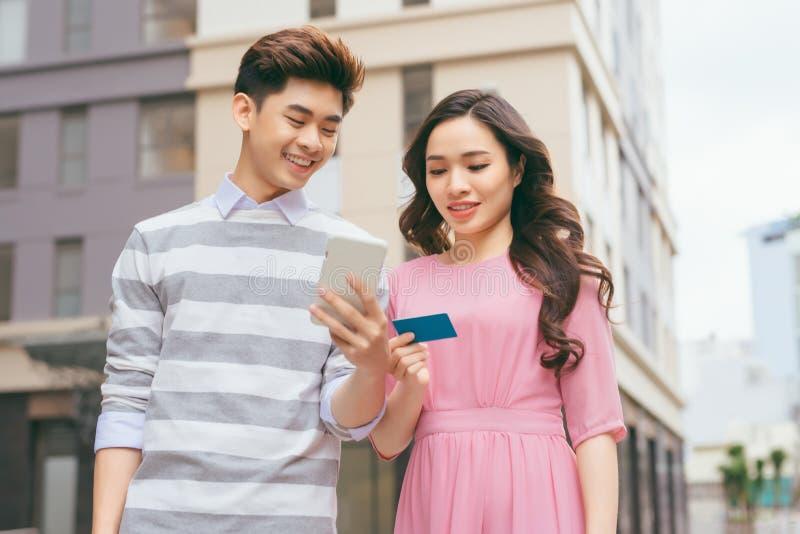 Mooi Aziatisch paar die met een creditcard in de stad winkelen stock foto's