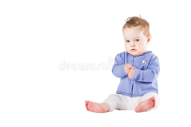 Mooi babymeisje die een purpere sweater dragen die haar handen slaan royalty-vrije stock foto
