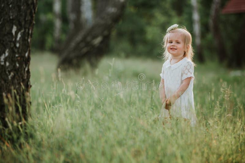 Mooi babymeisje die in een zonnige tuin met een mand lopen meisje in een witte kleding met een mand in het park royalty-vrije stock foto