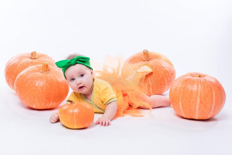 Mooi babymeisje in een geel lichaam met groene boog op haar hoofd stock afbeelding